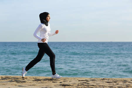 Arab saudi runner woman running on the beach with the sea and horizon in the background              Stock Photo