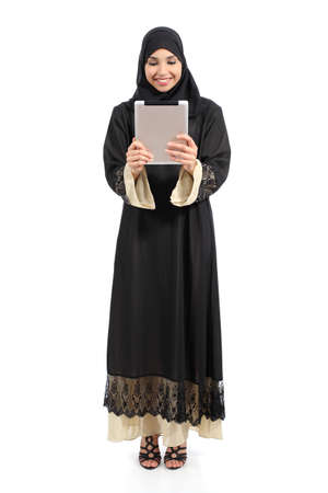 Arab saudi woman standing looking a tablet reader isolated on a white background