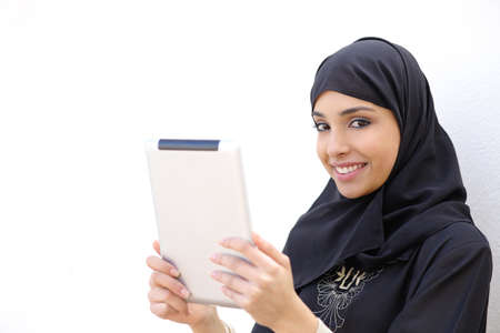 arab teen: Arab woman holding a tablet and looking at camera on a white wall background
