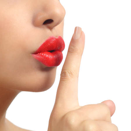 Close up of a woman lips with finger asking for silence isolated on a white background              photo