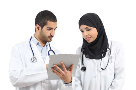 learning arabic: Saudi arab doctors diagnosing looking a medical history isolated on a white background               Stock Photo