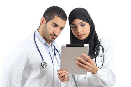 learning arabic: Saudi arab doctors working with a tablet isolated on a white background Stock Photo
