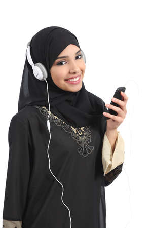 Saudi arab woman listening to the music from a smart phone and looking at camera isolated on a white background           photo