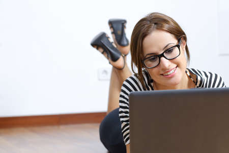Portrait of a beautiful woman with glasses browsing a laptop at home lying on the floor  photo