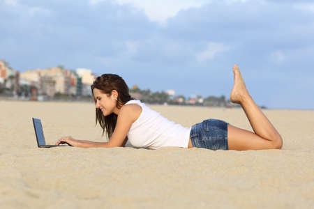 Profile of a teenager girl browsing her laptop lying on the sand of the beach with a city in the background              photo