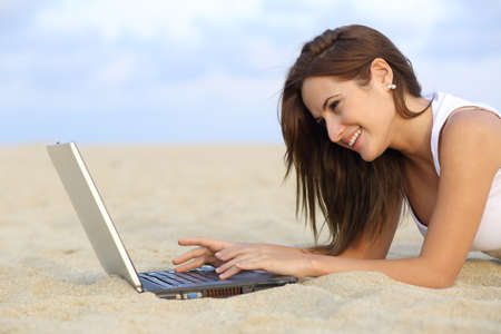 Side view of a teenager girl browsing her laptop lying on the sand of the beach with the horizon in the background photo