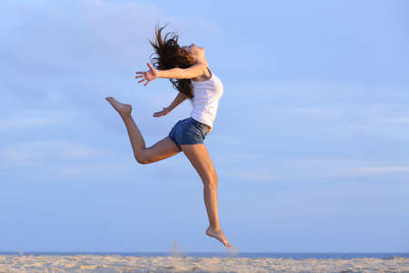 Woman jumping on the sand of the beach with the horizon in the background