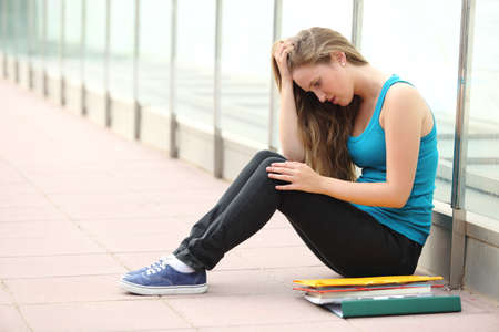 Beautiful student teenager girl depressed sitting on the floor outdoor  Stock Photo