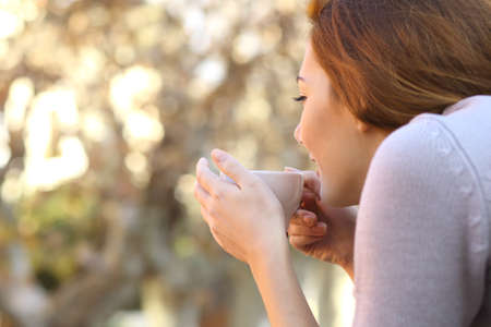 Wellness concept of a relaxed woman holding a cup of coffee outdoor
