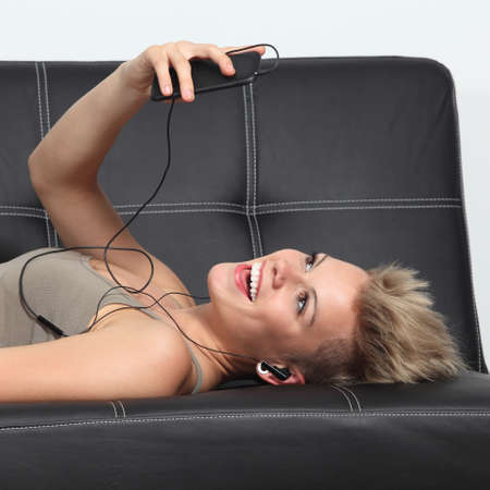 Profile of a woman at home lying on a couch listening to the music from a smartphone                photo