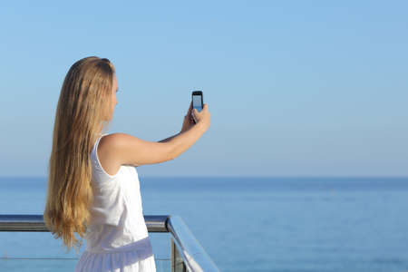Woman making a photograph of the sea with a smart phone with the horizon over the sea in the background             photo