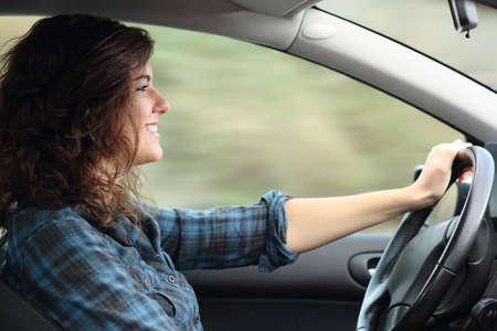 Perfil de uma mulher feliz dirigindo um carro com borr