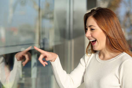 Beautiful woman looking a storefront surprised and pointing with the finger photo