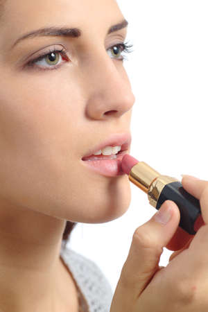 Close up of a beautiful woman applying a lipstick on lips isolated on a white background photo
