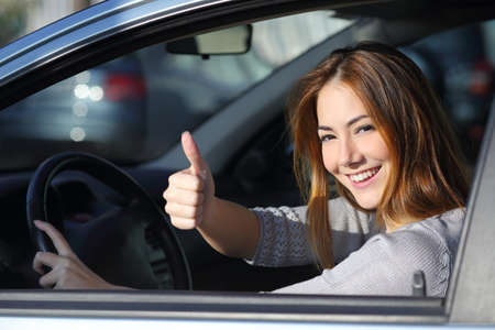 Happy woman inside a car driving in the street and gesturing thumb up photo