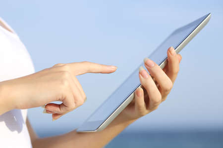 Profile of a woman hands holding and browsing a digital tablet on the beach with the sky in the background photo
