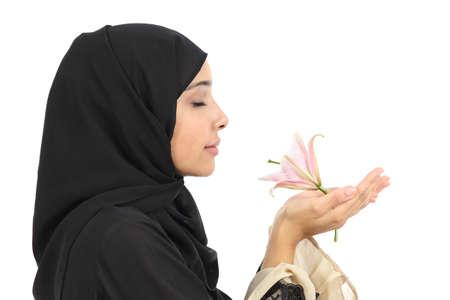 白い背景で隔離の花の臭いがするアラブの女性のプロファイルのクローズ アップ 写真素材