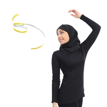 Arab saudi fitness woman throwing a measure tape isolated on a white background