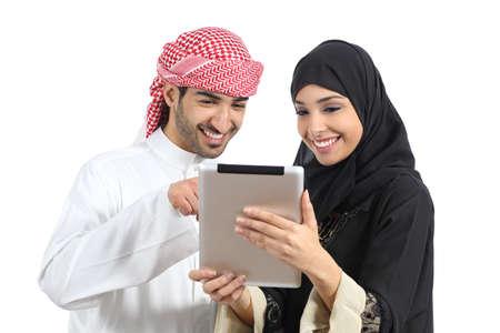Árabe saudi pareja feliz navegando un lector de la tableta aislado en un fondo blanco Foto de archivo