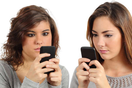 cell phone addiction: Two teenagers addicted to the smart phone technology isolated on a white background