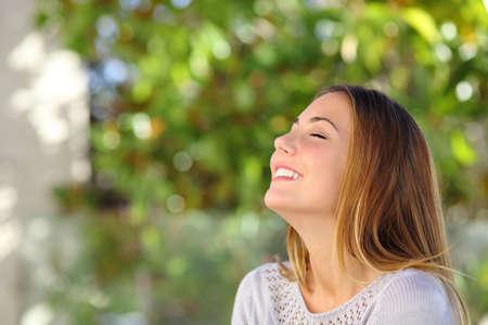 緑の背景で屋外深呼吸の演習を行う若い幸せな笑顔の女性 写真素材