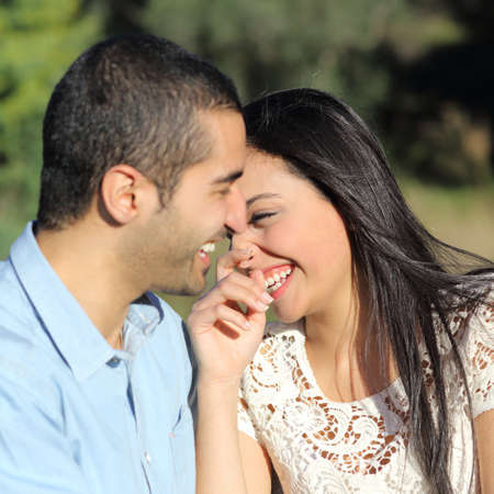 Close up of an arab casual couple flirting and laughing happy in a park photo