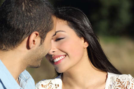 Close up of an arab casual couple flirting ready to kiss with love in a park             photo