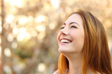 Portret van een vrouw lachend met een perfecte tanden op een warme achtergrond
