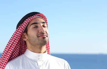Hombre saudi árabe respirar aire fresco profundamente en la playa con el océano y el horizonte en el fondo Foto de archivo