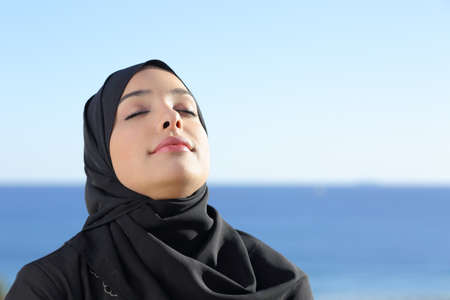 Arab saudi woman breathing deep fresh air in the beach with the ocean and horizon in the background