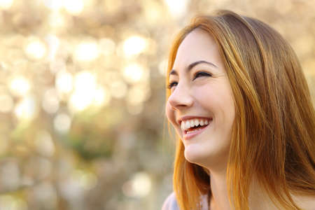 Gezicht portret van een grappige vrouw gezicht lachen met een warme achtergrond Stockfoto