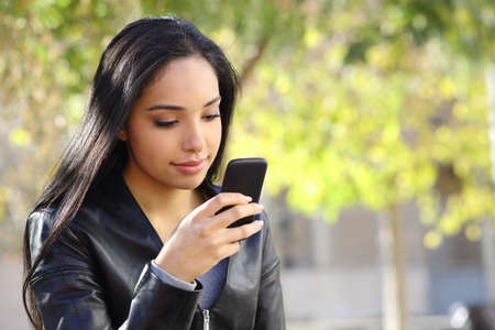 Beautiful woman texting on a smart phone in a park with a green background photo