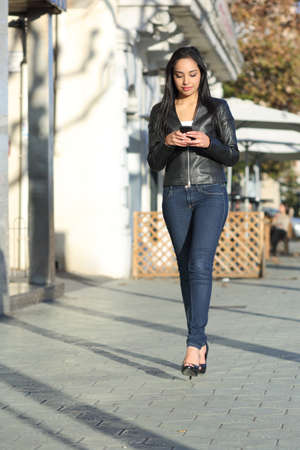 handphone: Happy casual woman walking in the street writing in a smart phone