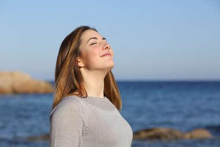 バック グラウンドでホライズンと共にビーチに深い新鮮な空気を呼吸幸せなリラックスした女