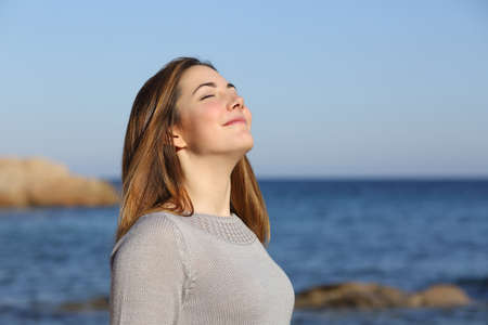 Happy relaxed woman breathing deep fresh air on the beach with the horizon in the background photo