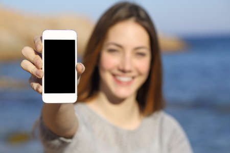 백그라운드에서 바다와 해변에서 스마트 폰 화면을 보여주는 행복한 여자
