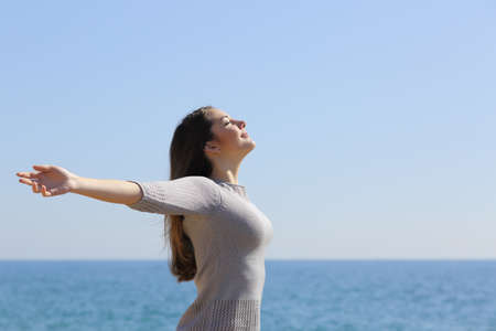 Happy relaxed woman breathing deep fresh air and raising arms on the beach with the horizon in the background