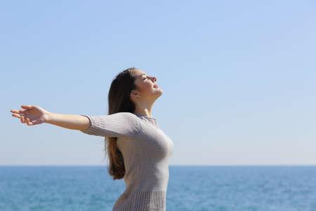 aire puro: Mujer relajada feliz respirando aire fresco y profundo que levanta los brazos en la playa con el horizonte en el fondo