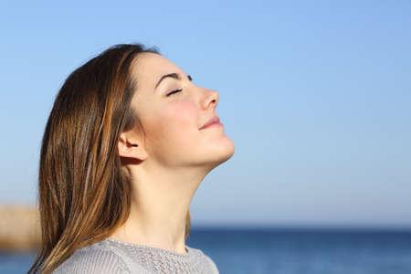 aire puro: Perfil de la mujer del retrato de respiración de aire fresco profundamente en la playa con el mar de fondo Foto de archivo