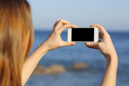 Back view of a woman taking photograph with a smart phone camera at the horizon on the beach      photo