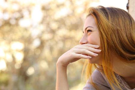 幸せな女彼女の暖かさの背景を持つ手で口を覆っている笑っています。