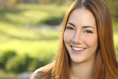 Portrait of a woman white smile dental care in a park with a green warmth background               Stock Photo