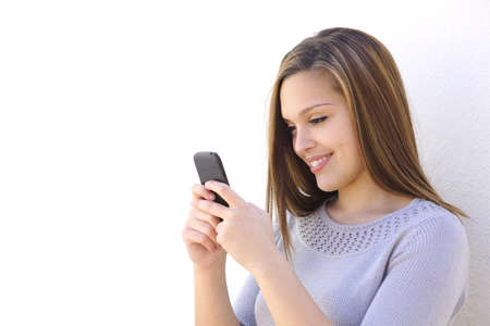 Happy woman texting on a smartphone looking at phone on a white wall         photo