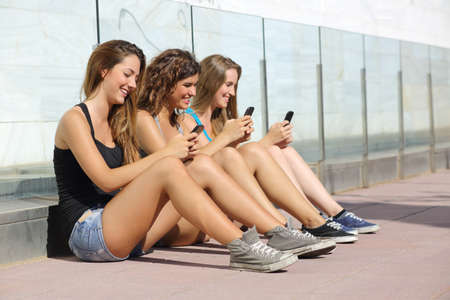 Group of teenager girls smiling happy texting on the smart phone sitting on the floor outdoors photo