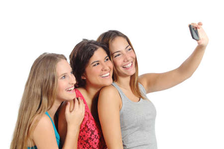 Group of teenager girls taking a photograph with the smart phone camera isolated on a white background              photo