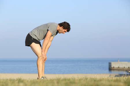 バック グラウンドで海でトレーニングの後、ビーチで休んで疲れランナー男