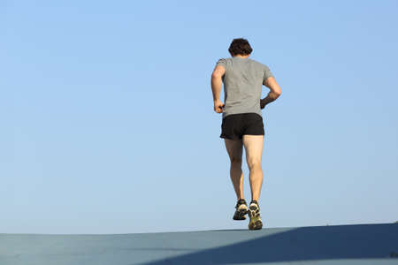 towards: Back view of a jogger man running against blue sky with copy space