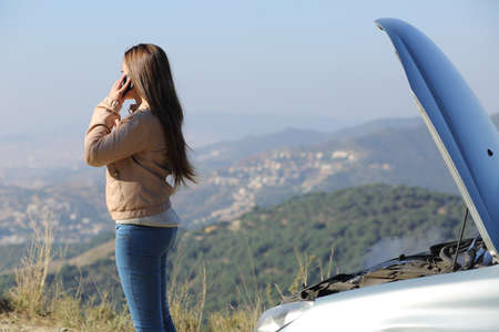 Woman on the phone asking for assistance beside her crashed breakdown car in a mountain road photo