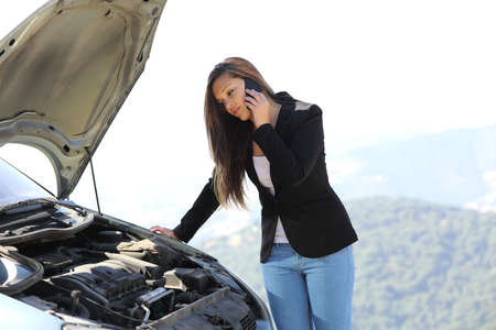 Woman on the phone looking her crash breakdown car in a road in the middle of the mountain