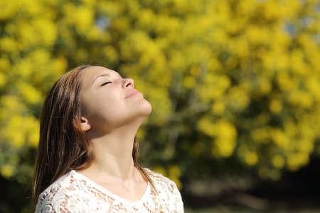 persona respirando: Mujer que respira profundamente en la primavera o el verano con un fondo amarillo Foto de archivo